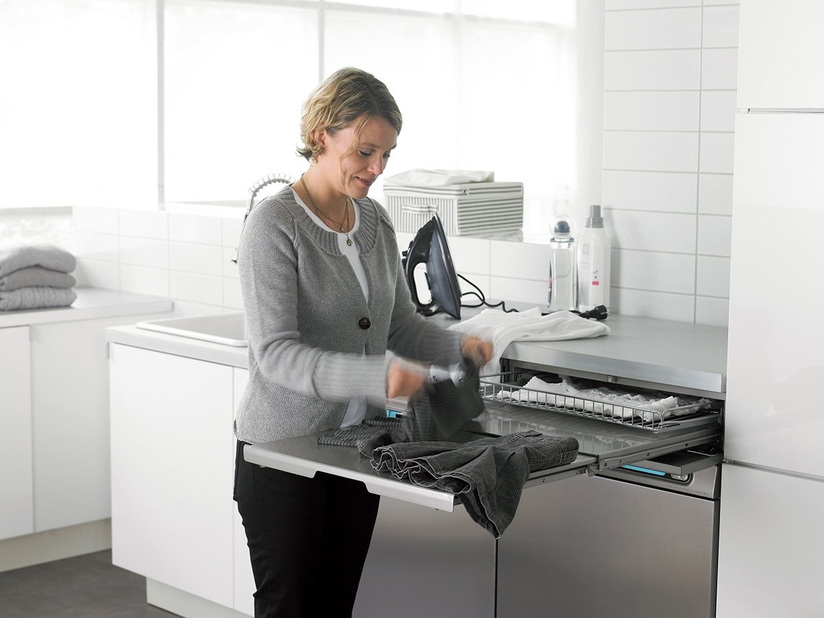 Woman using an ASKO washer and Dryer in a white room